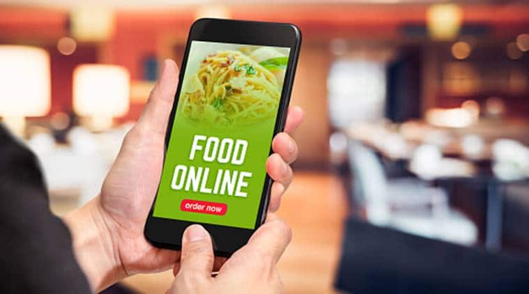Close up hand holding mobile phone with order food online word on screen with blur restaurant bokeh light background,online food marketing concept